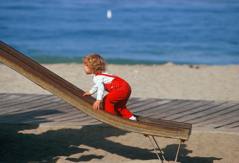 Download Little Girl In Red Overralls Climbing Up Slide Editorial Stock Image - Image: 23149749