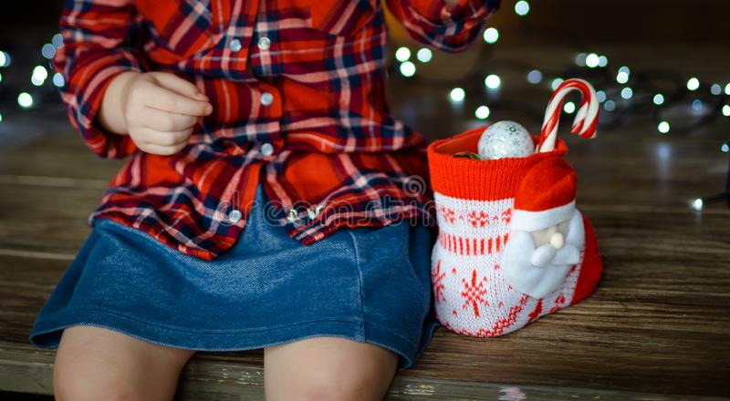 A little girl in a red plaid shirt and a denim blue skirt, opens the sweets from her Christmas gif. T, sitting on a wooden table. Christmas morning concept royalty free stock images