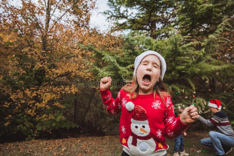 Little girl in red sweater and Christmas hat is upset when her family decorates a Christmas tree in the background royalty free stock images