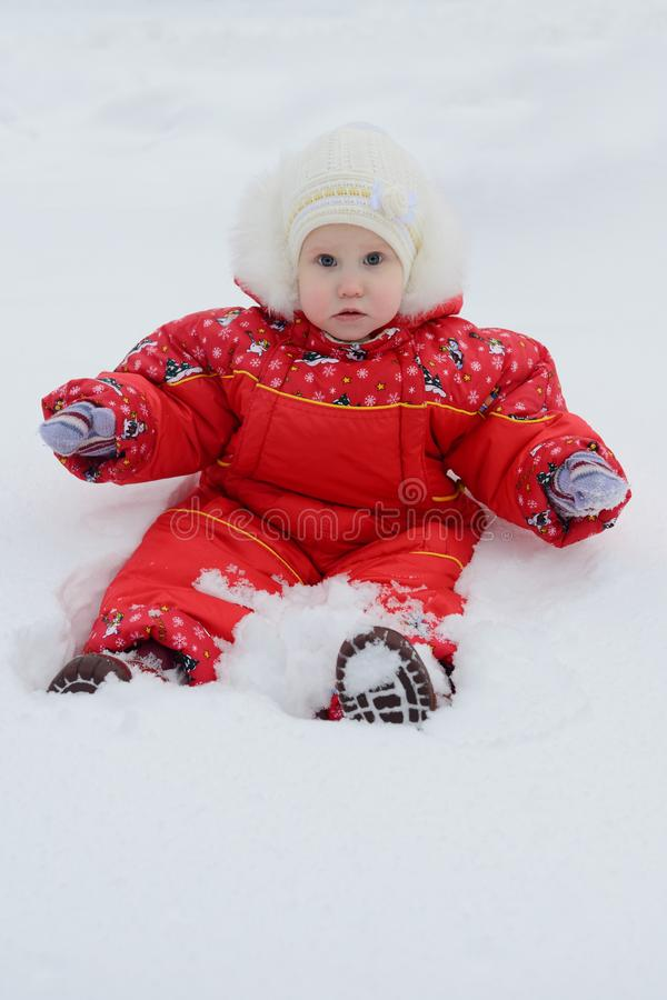 little girl in winter jumpsuit surprised in a snowdrift stock photos