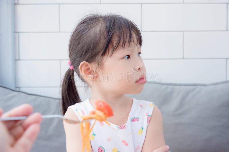 Little girl refuse to eat tomato in spagethi from her mother stock photos