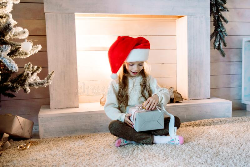 Little girl rejoices gift near the fireplace.Christmas is coming. Home interior christmas tree decoration. santa claus hat stock photos