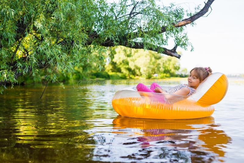 Little girl relaxes in an inflatable chair, floating on the water royalty free stock photo
