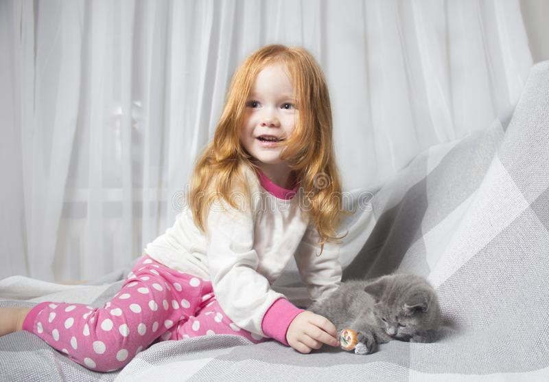 Little girl relaxing on the bed with her kitten. Child is kissing a cat stock photo