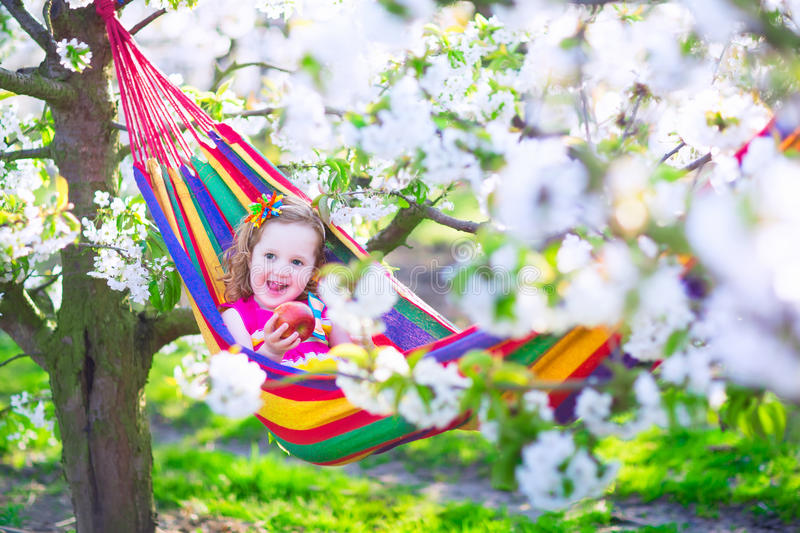 Little girl relaxing in a hammock royalty free stock image