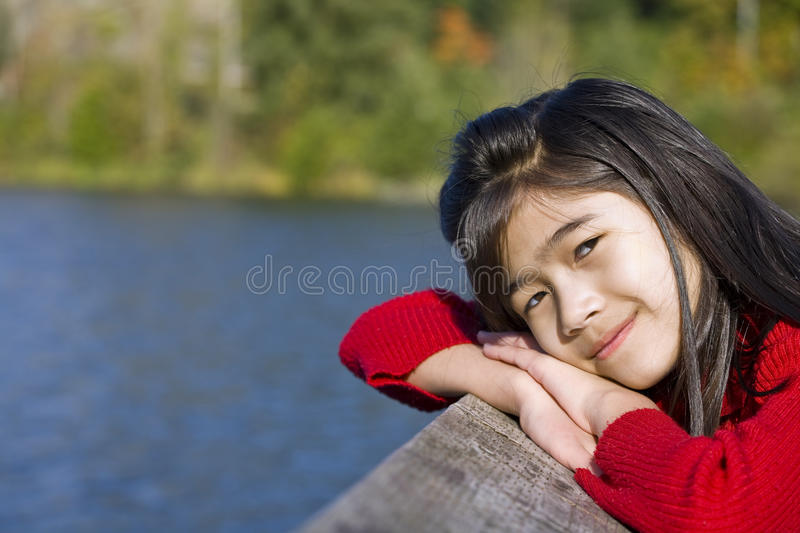 Little girl relaxing by lake. Little asian girl relaxing by lake royalty free stock photography
