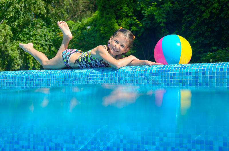 Little girl relaxing near pool, underwater and above view. Kid on summer vacation stock photo