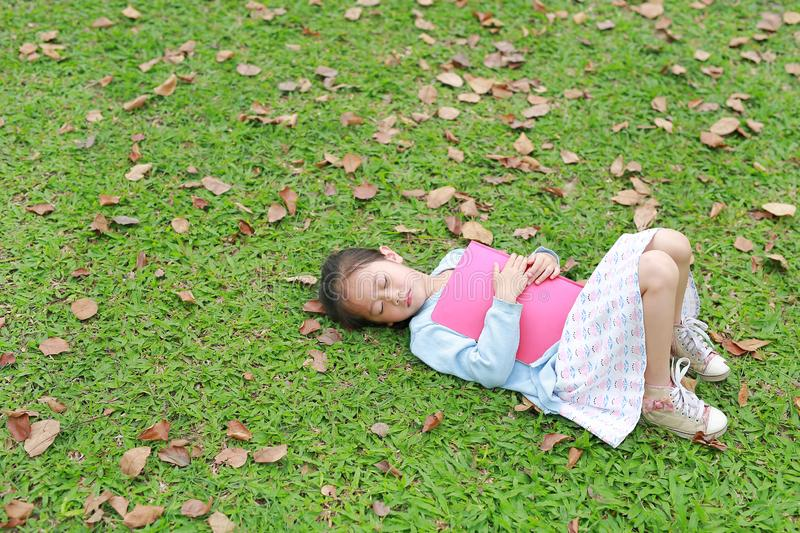 Little girl resting with book lying on green grass with dried leaves in the summer garden royalty free stock image