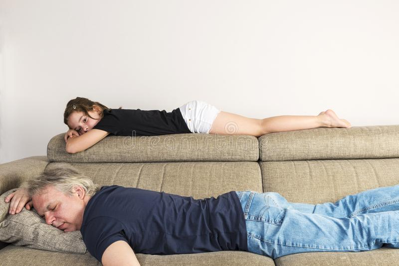 Little girl resting with her dad on the couch at home stock images