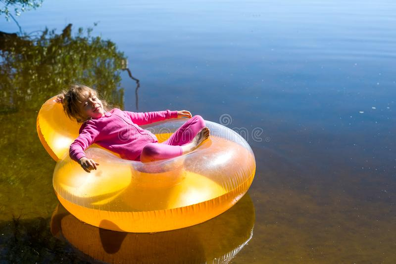 The little girl is resting in an inflatable chair, floating on the water royalty free stock image