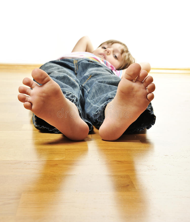 Little girl resting on a wooden floor royalty free stock photos