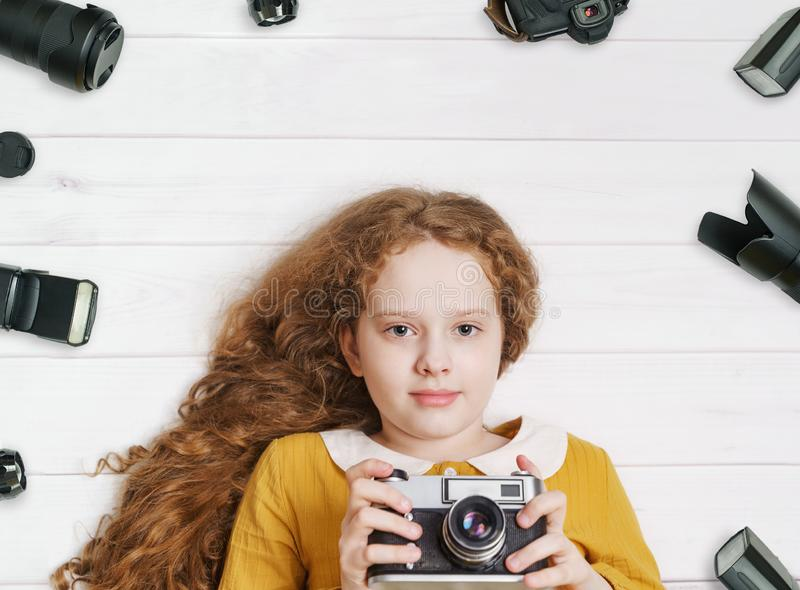 Little girl with retro photo cameras and photo accessoires. Lying on a wooden floor stock photos