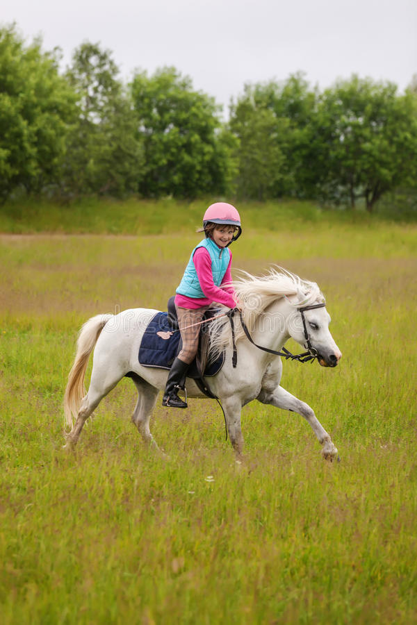Little girl rides a beautiful horse royalty free stock images
