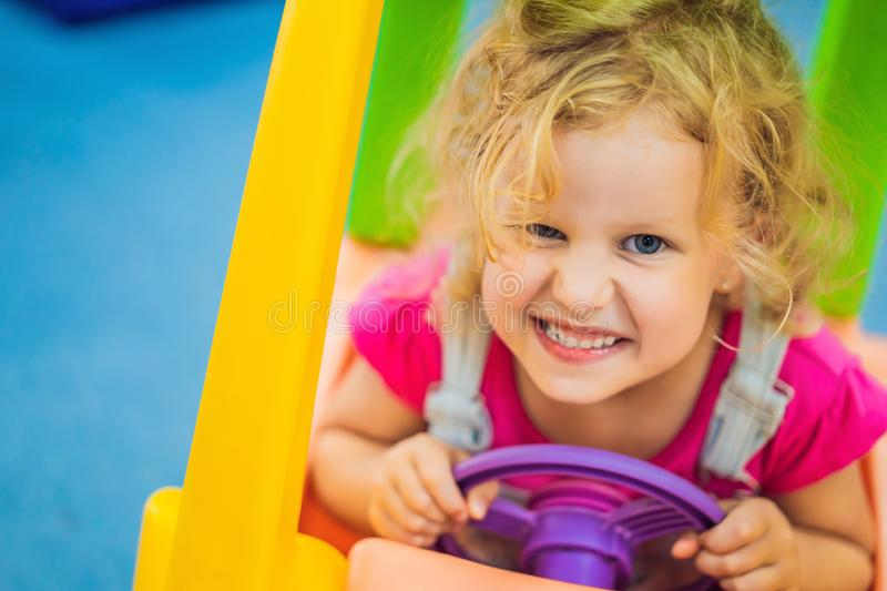 Little girl rides a toy colorful car royalty free stock photo