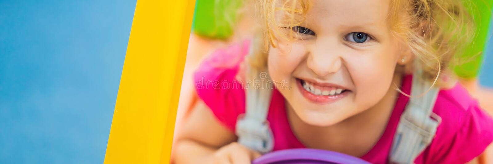 Little girl rides a toy colorful car BANNER, LONG FORMAT stock photography