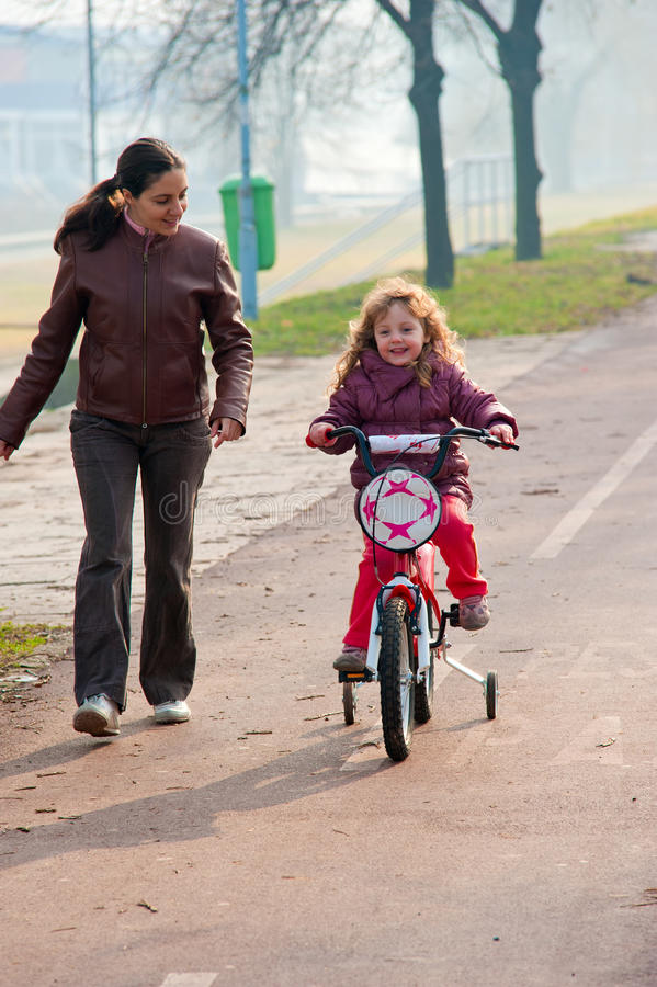 Download Little Girl Riding A Bike, Bycicle With Mother Royalty Free Stock Images - Image: 17988139