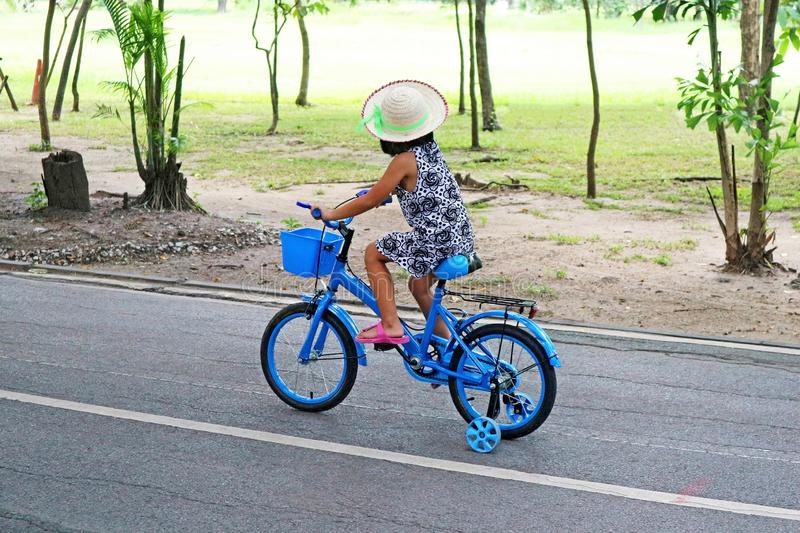 Little Girl Riding a Blue Bicycle stock photography