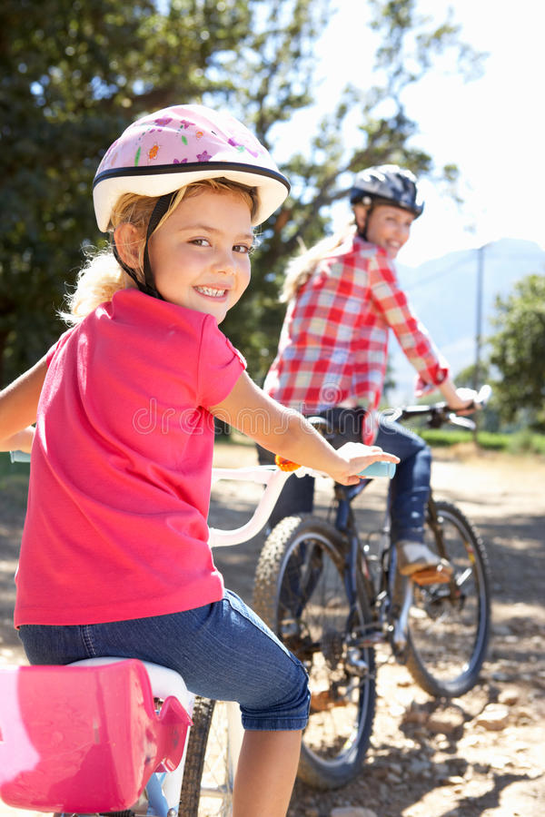 Little girl riding through country with mum