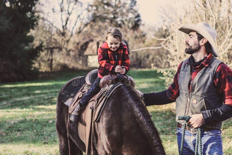 Little Girl Riding Horse Beside Man royalty free stock photos