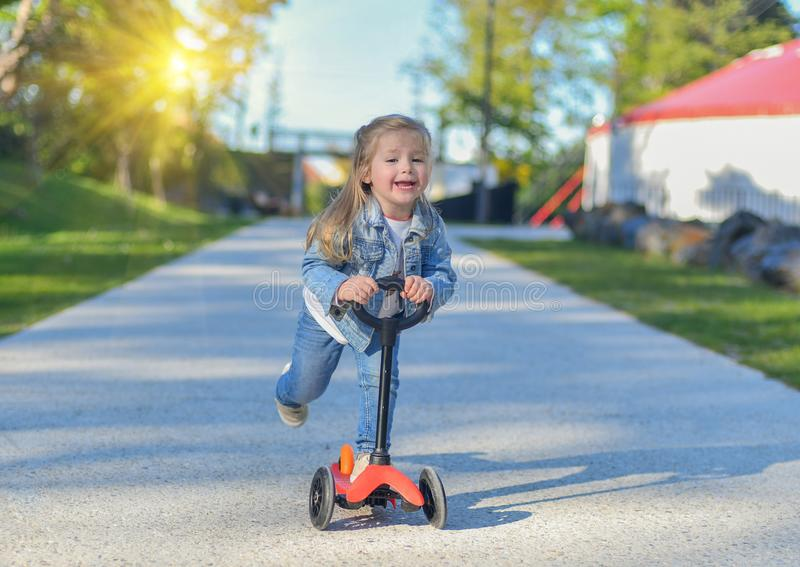 Little girl is riding a scooter stock images