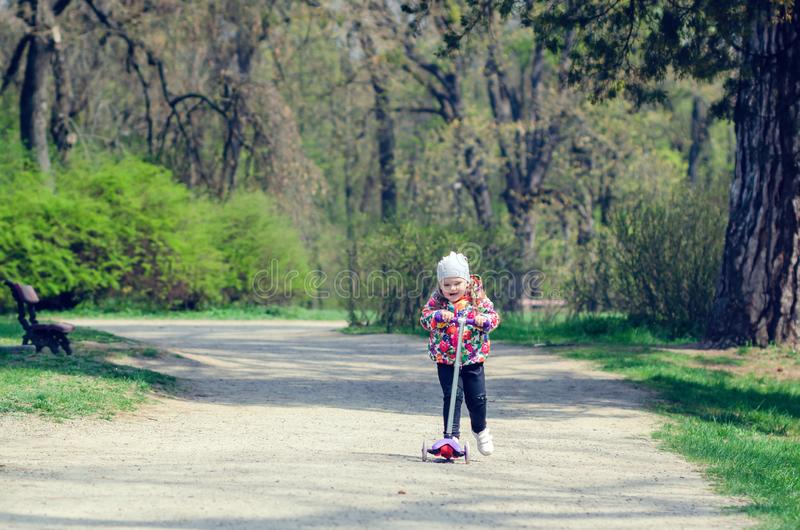 Little girl riding a scooter in the spring park.  royalty free stock image
