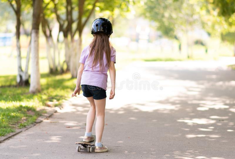 A little girl is riding a skateboard from the back. For any purpose royalty free stock images