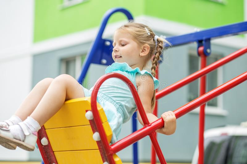 Little girl is riding on a swing. The concept of childhood, lifestyle, upbringing, kindergarten. Little girl is riding on a swing. The concept of childhood royalty free stock image