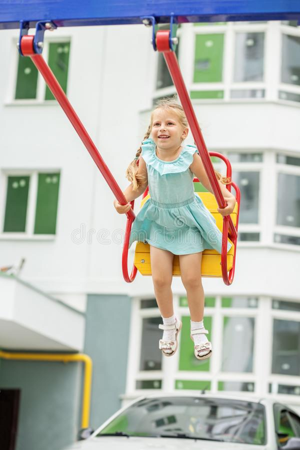 A little girl is riding a swing and laughing. The concept of childhood, lifestyle, upbringing, kindergarten. A little girl is riding a swing and laughing. The stock images