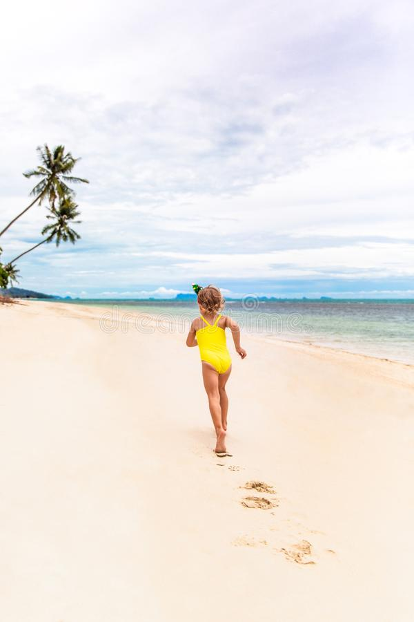 Little girl in the rim in the form of Christmas trees and yellow swimsuit is runing on the beach royalty free stock photography