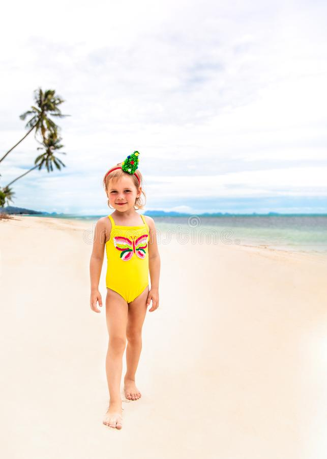 Little girl in the rim in the form of Christmas trees and yellow swimsuit is standing on the beach royalty free stock images