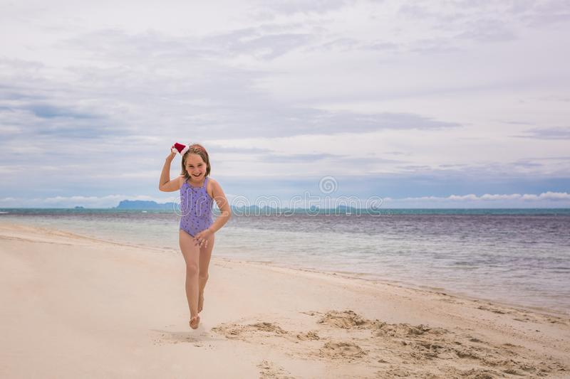 Little girl in the rim in the form of Christmas trees and yellow swimsuit is standing on the beach stock photos