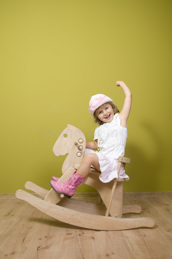 Little girl and rocking horse royalty free stock images