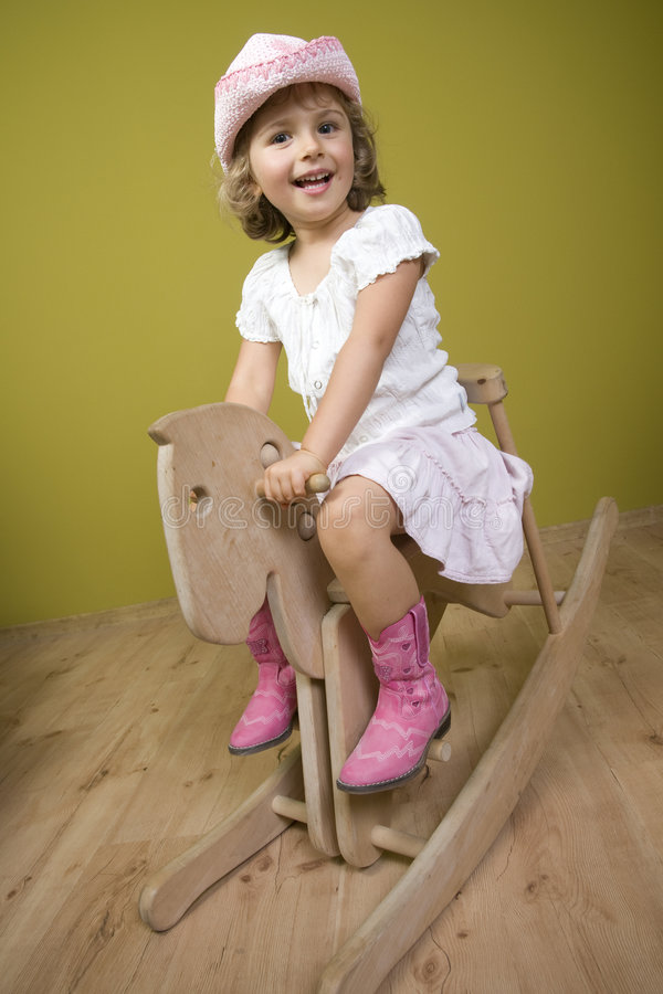 Little girl and rocking horse stock images