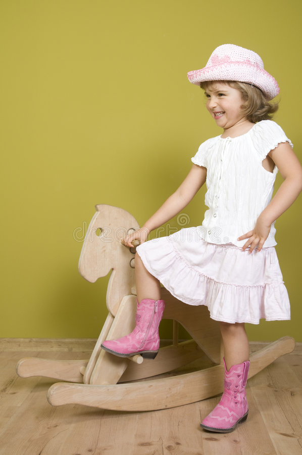 Little girl and rocking horse stock photography