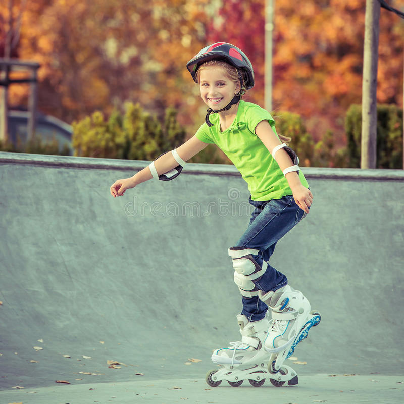 Little girl on roller skates. In helmet at a park royalty free stock photography