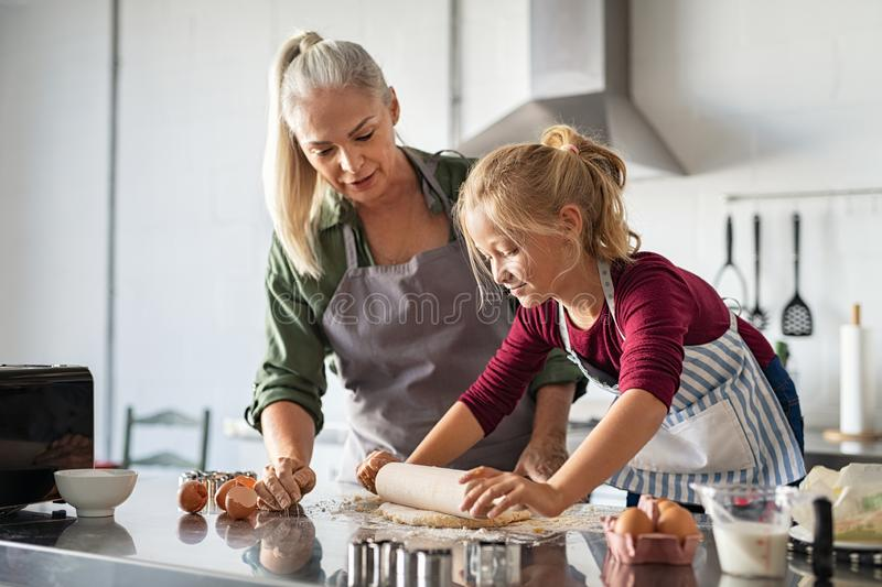Little girl rolling dough with grandmother stock image