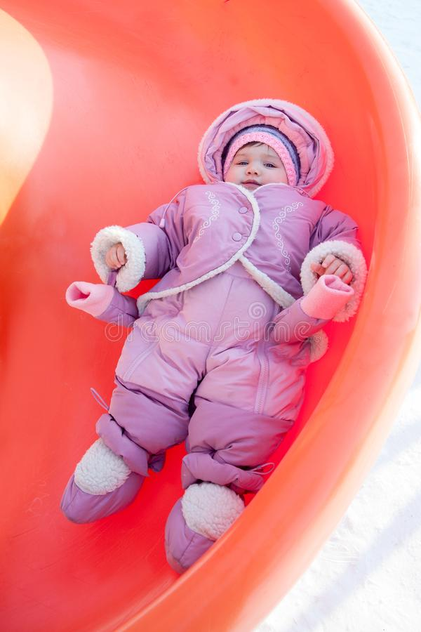 Little girl rolling downhill on a winter da. Y stock photography