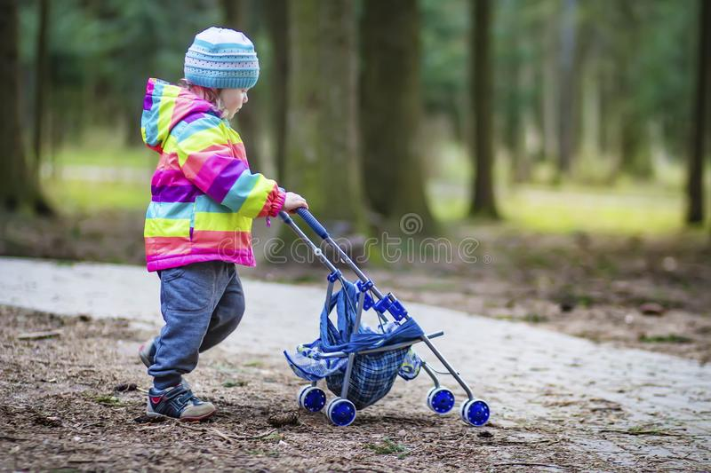 A little girl is rolling toy baby carriage in the park. Child in the park playing with pram. royalty free stock image