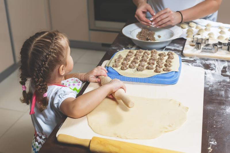 Little girl rolls out the dough, while her mother sculpts the dumplings for the holiday royalty free stock photography