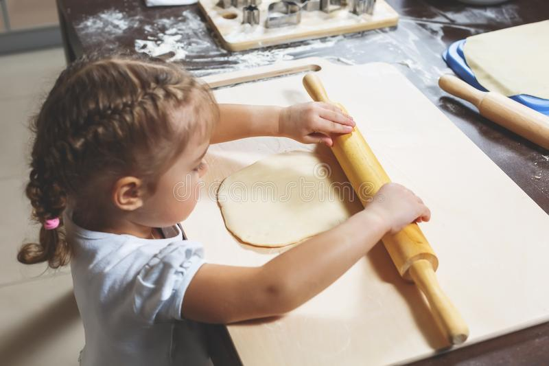 Little girl rolls out the dough with a large rolling pin for making homemade cookies stock photo