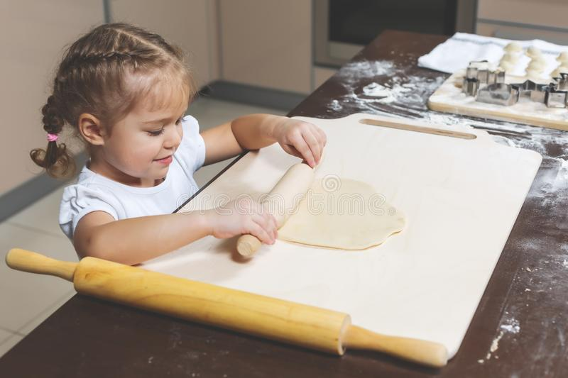 Little girl rolls out the dough with a small rolling pin royalty free stock photos