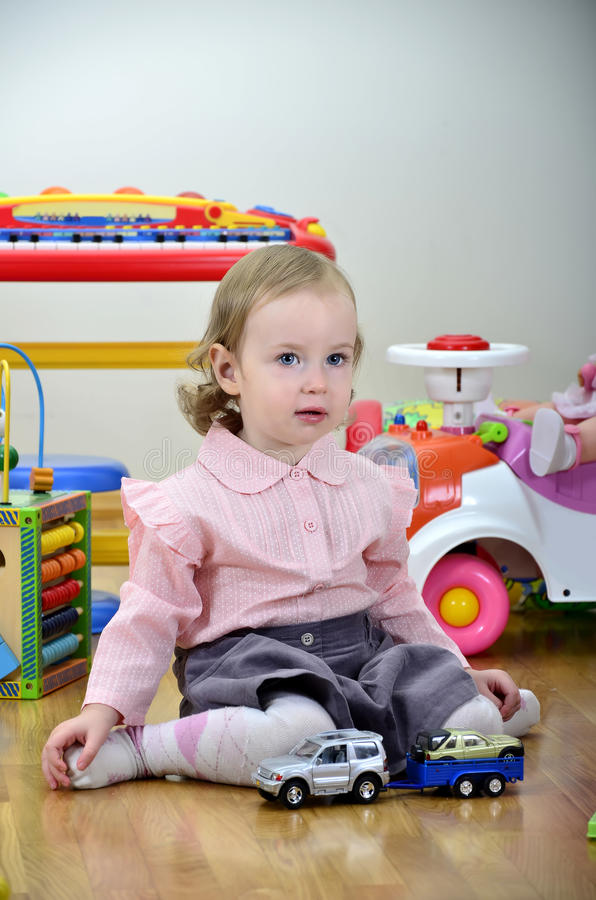 Little girl in a room with toys. Playing with cars royalty free stock photos