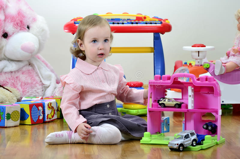 Little girl in a room with toys. Playing with cars royalty free stock image