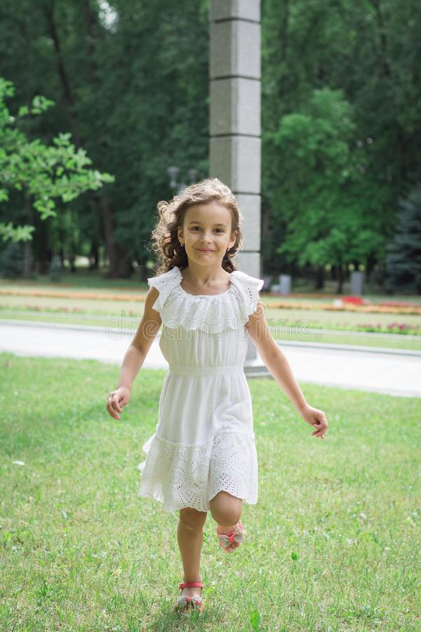 Little girl run in autumn or summer park. Happy child royalty free stock photo