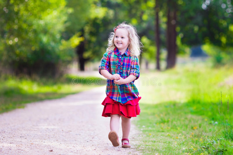Little girl running in autumn park royalty free stock photo