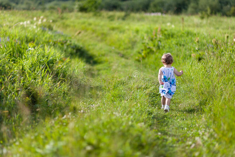 Little girl running away in meadow stock image