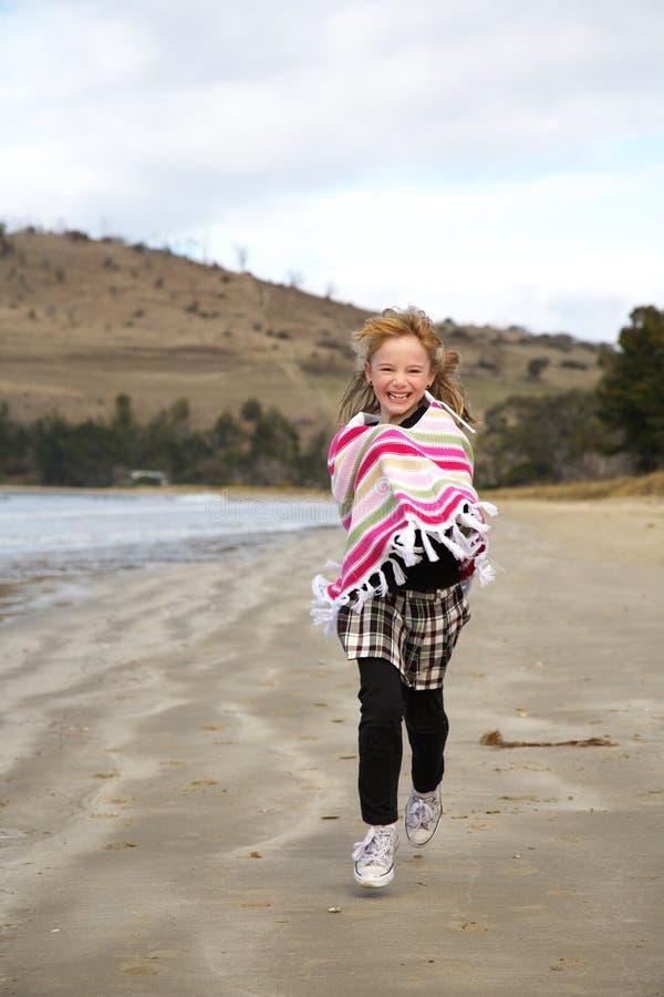 Little girl running on beach stock image