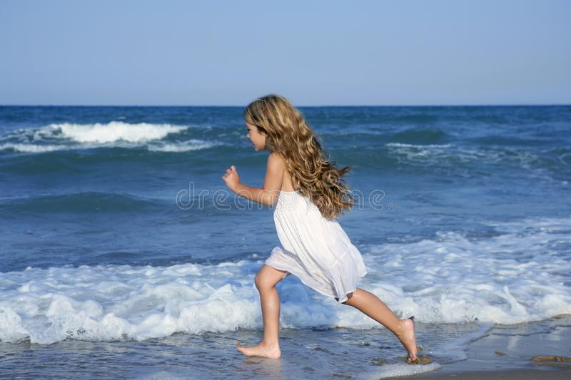 Little girl running beach in blue sea royalty free stock image