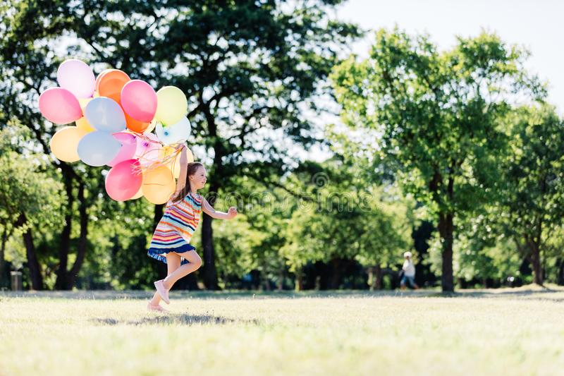 Little girl running fast with a bunch of colorful balloons royalty free stock images
