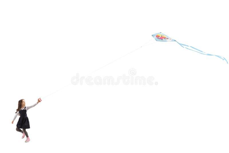 Little girl running and flying a kite stock image